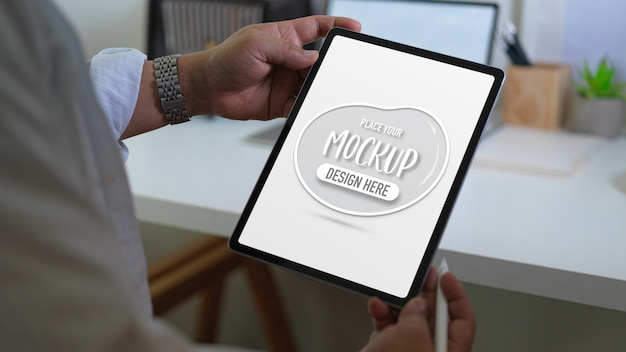 Close up view of businessman holding mockup digital tablet and stylus pen Premium Psd