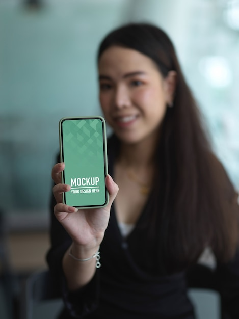 Close up view of businesswoman showing mock up smartphone screen in office room Premium Psd