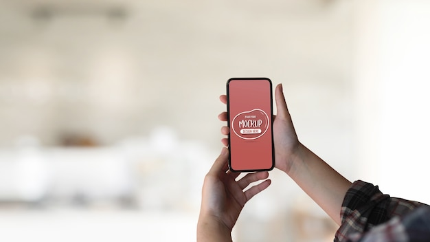 Close up view of female hand holding mock up smartphone Premium Psd