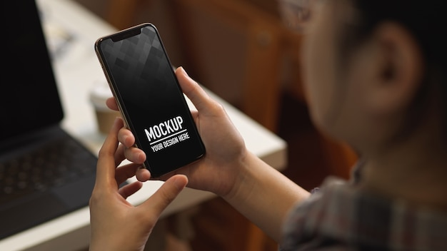 Close up view of female using smartphone mockup while working in office room Premium Psd