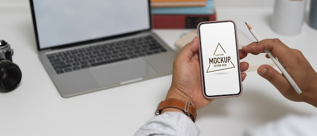 Close up view of male entrepreneur using mock up smartphone while working with laptop on worktable Premium Psd