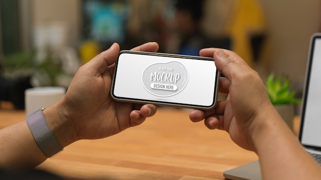 Close up view of male hands holding mock up horizontal smartphone screen in workplace Premium Psd