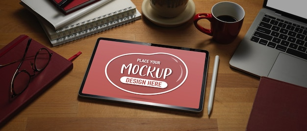 Close up view of mock up digital tablet on wooden worktable with laptop and supplies Premium Psd