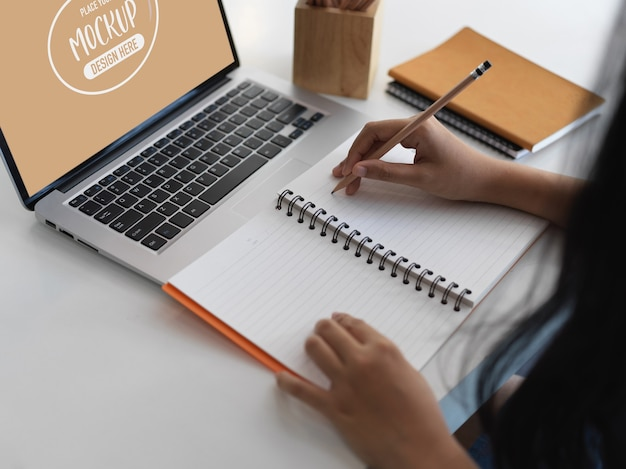 Close up view of office worker writing on notebook while using screen laptop mockup Premium Psd