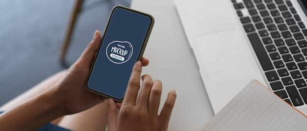 Крупным планом вид на руках смартфон с макетом экрана Premium Psd