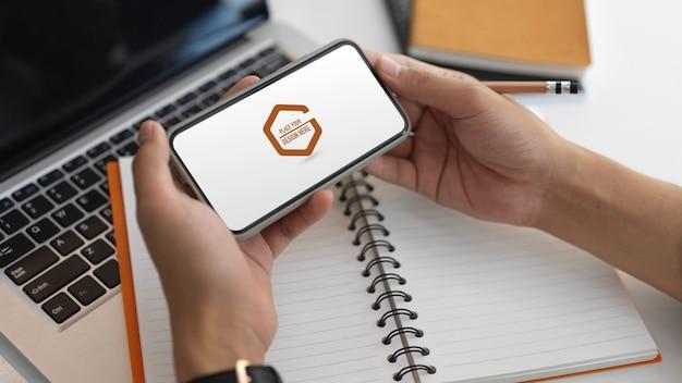 画面のモックアップとスマートフォンを持っている手のビューをクローズアップ Premium Psd