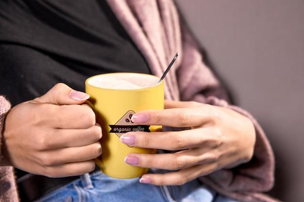 黄色のマグカップを持つクローズアップ女性 無料 Psd