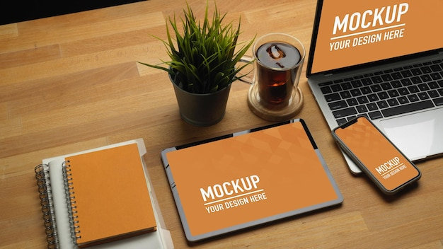 Close up of wooden table with tablet, smartphone, laptop mockup Premium Psd
