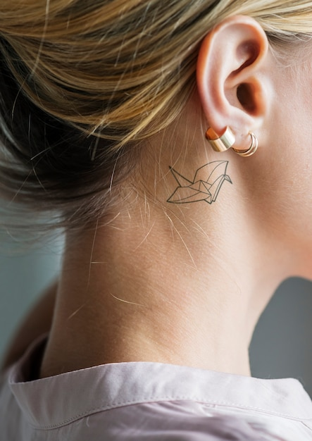 Closeup of a simple behind the ear tattoo of a young woman Free Psd