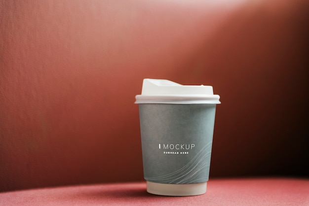 Coffee cup mockup in a red backdrop Free Psd