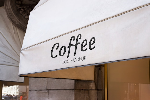 Coffee shop logo mockup on white awning. traditional look of white white set in front of window Premium Psd