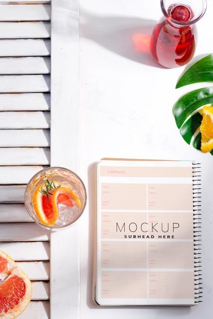 Cold summer homemade cocktail in a glass with slice of grapefruit and and paper note book Premium Psd