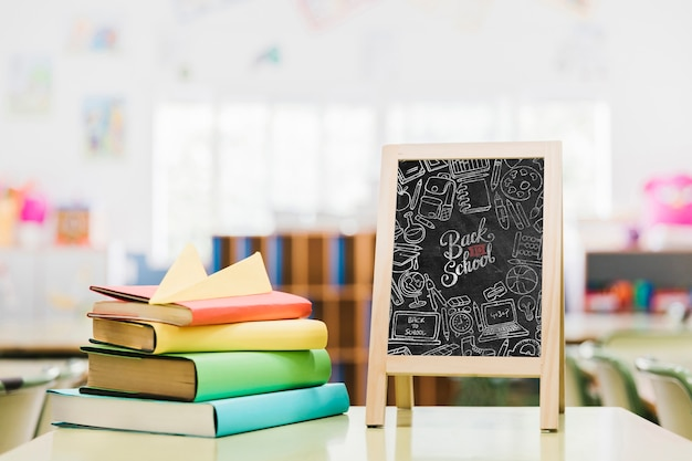 Colorful books next to school blackboard mock-up Free Psd