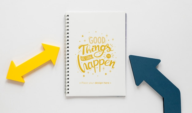 Colourful arrows and notebook mock-up Free Psd