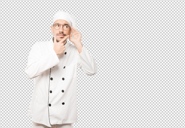 Concentrated young chef making a gesture of trying to hear something Premium Psd