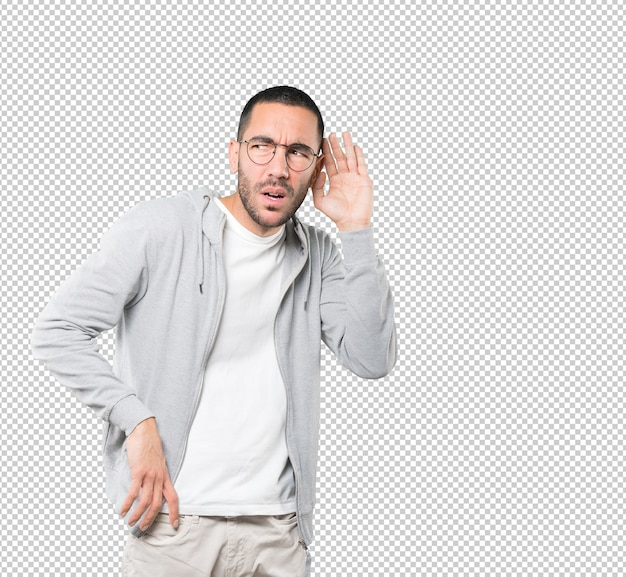 Concentrated young man making a gesture of trying to hear something Premium Psd