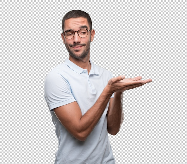 Concept of a happy young man holding something with his hand Premium Psd