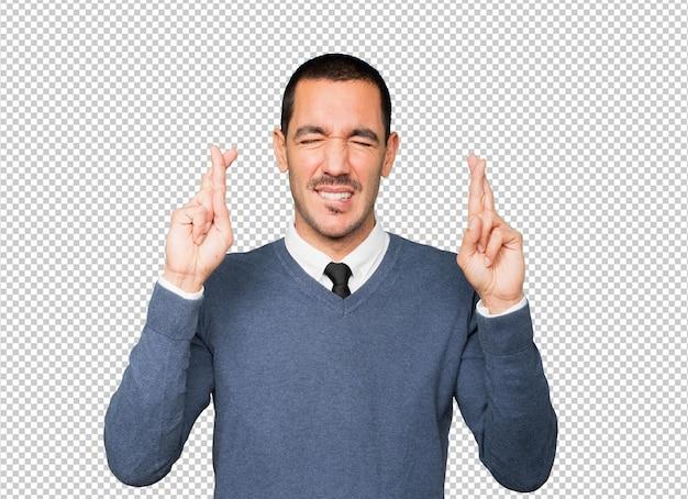 Обеспокоенный молодой человек делает жест скрещенными пальцами Premium Psd