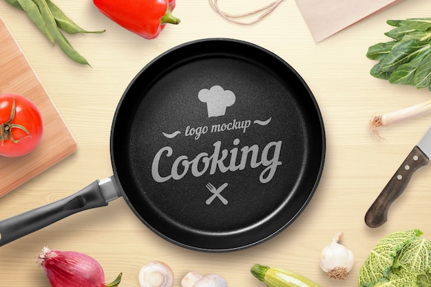 Cooking, restaurant logo mockup. pan on the kitchen table surrounded by vegetables. top view, flat lay Premium Psd