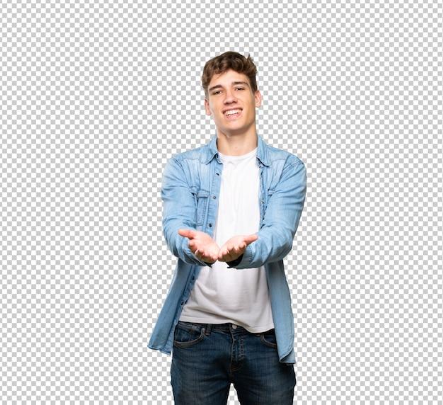 ハンサムな若い男が広告を挿入する手のひらに想像上copyspaceを保持 Premium Psd