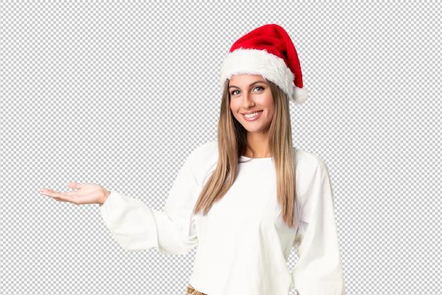 Блондинка с рождественской шляпой держит на ладони copyspace мнимой Premium Psd