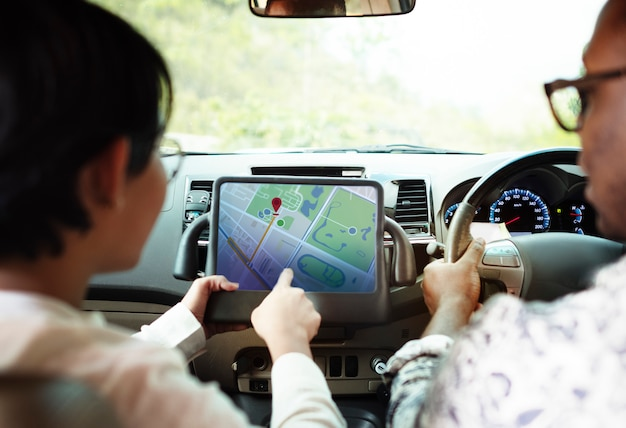 Couple in a car finding direction on a tablet with gps Premium Psd
