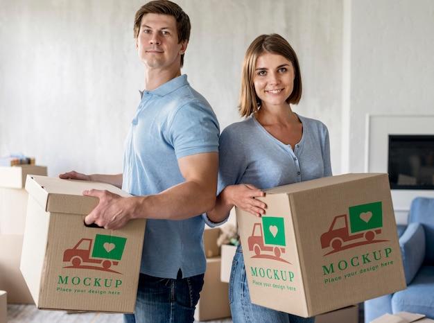 彼らの新しい家のために箱を持って幸せであるカップル 無料 Psd