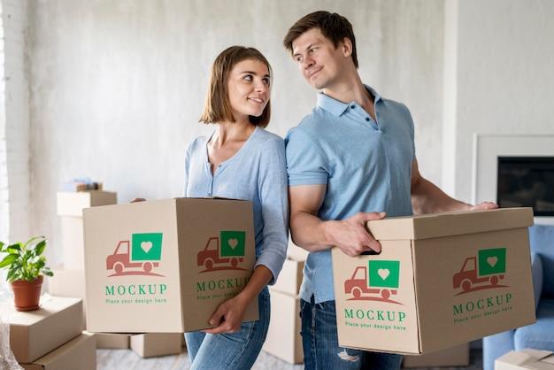 彼らの新しい家のために箱を持って、お互いを見ているカップル 無料 Psd