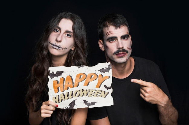 Couple holding paper with halloween lettering Free Psd