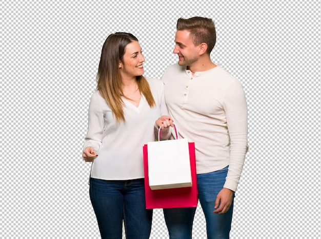 Couple in valentine day holding shopping bags in victory position Premium Psd