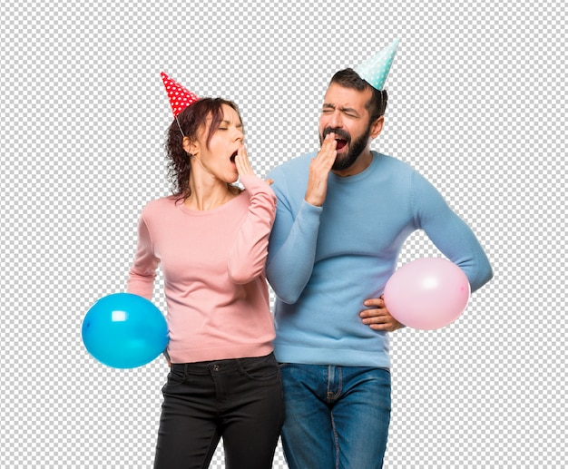 Couple with balloons and birthday hats yawning and covering mouth with hand. sleepy expression Premium Psd