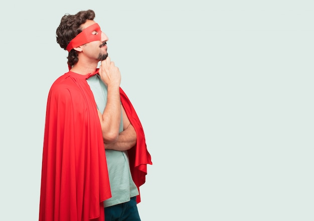 Crazy man as a super hero with a confused and thoughtful look, looking sideways, thinking Premium Psd