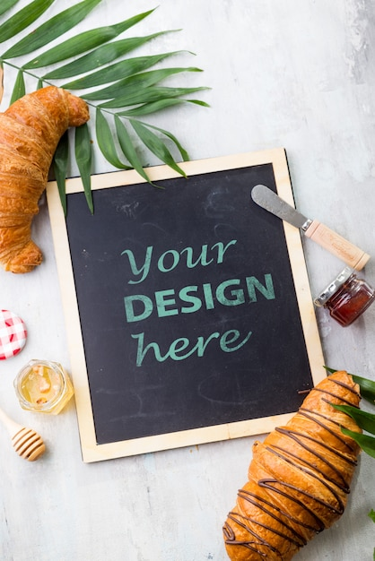 Croissant and jam with leaves palm, chalk board  flat lay mockup Premium Psd