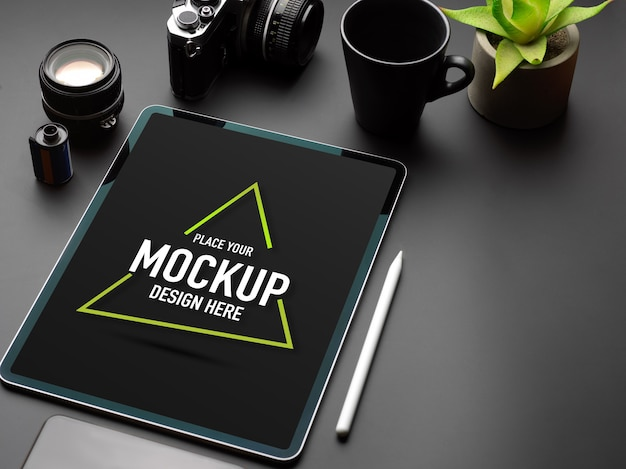 Cropped shot of black table with mock up tablet, camera, mug, plant pot and copy space Premium Psd