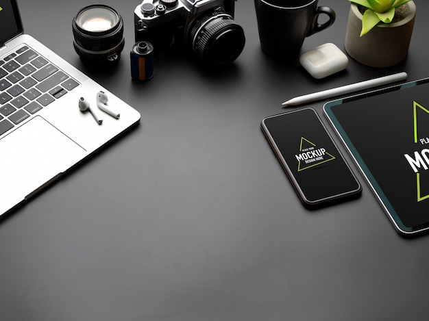 Cropped shot of black table with mock up tablet, smartphone, laptop, camera and copy space Premium Psd