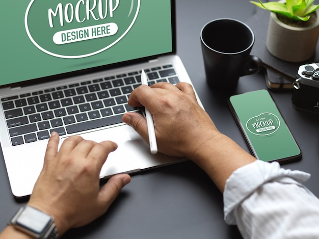 Cropped shot of male hands typing on laptop keyboard with mock up smartphone on black table Premium Psd