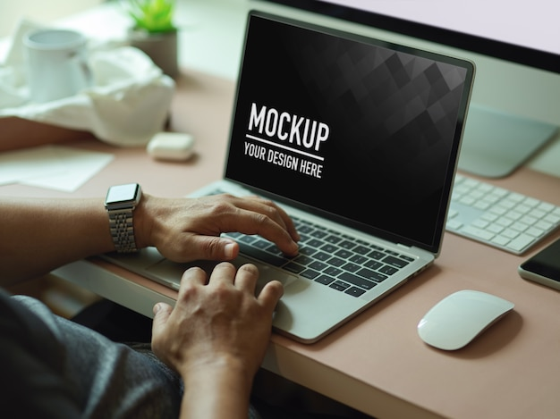 Cropped shot of male hands typing on mockup laptop Premium Psd