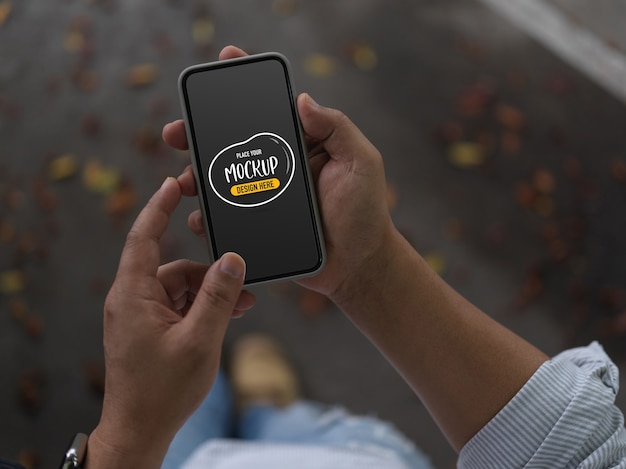Cropped shot of male using mockup smartphone while walking on street Premium Psd
