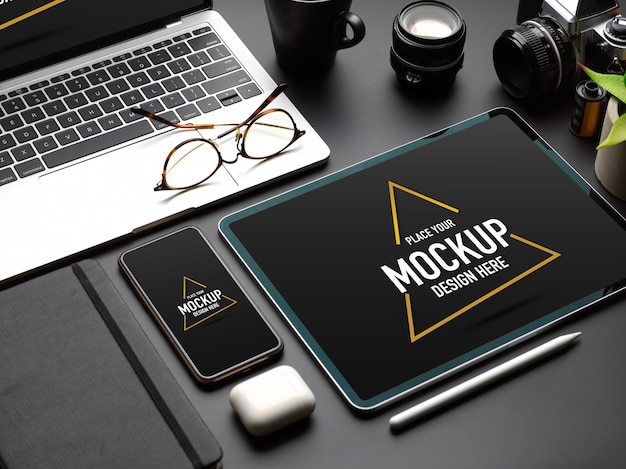 Cropped shot of mock up digital devices with tablet, smartphone and laptop on black table Premium Psd