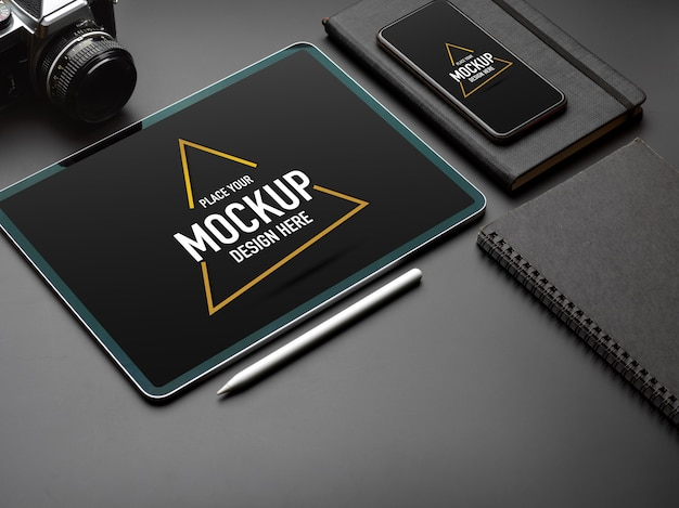 Cropped shot of mock up digital tablet, smartphone and camera on black table Premium Psd