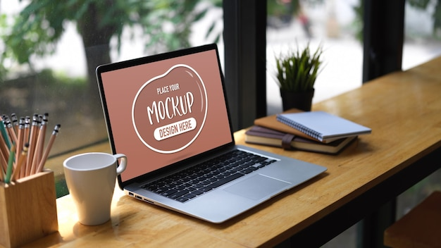 Cropped shot of mock up laptop, stationery, mug and plant pot on wooden bar in cafe Premium Psd