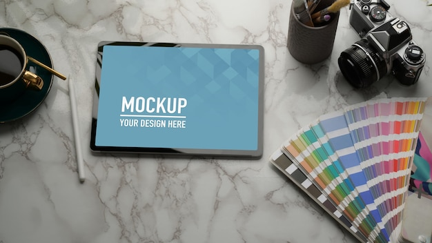Cropped shot of mock up tablet on marble table with camera, supplies and copy space Premium Psd
