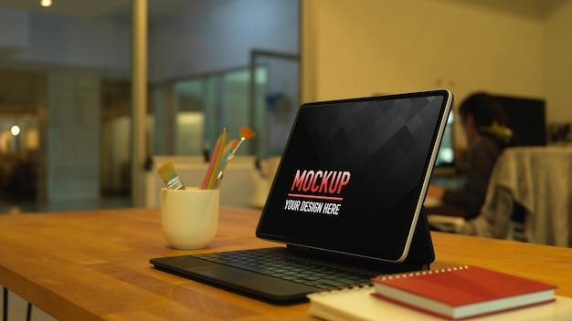 デジタルタブレット、ペイントブラシ、ノートブックを使用した作業台のクロップドショット Premium Psd