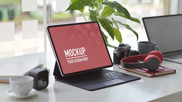 Cropped shot of workspace with mock up tablet, laptop, headphone, camera and supplies Premium Psd