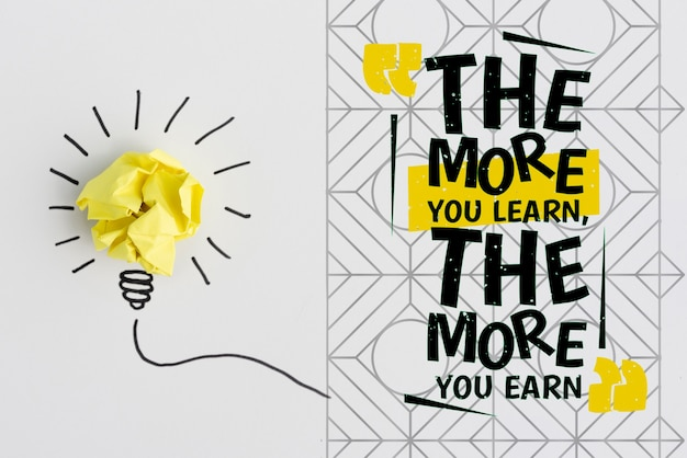 Crumpled paper in form of a light bulb and the more you learn, the more you earn quote Free Psd