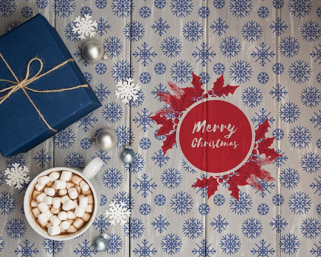 Cup with hot marshmellow and gift beside Free Psd
