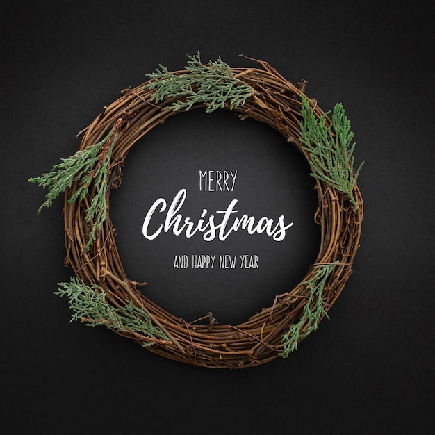 Cute christmas wreath on blackwith christmas tree leaves Free Psd