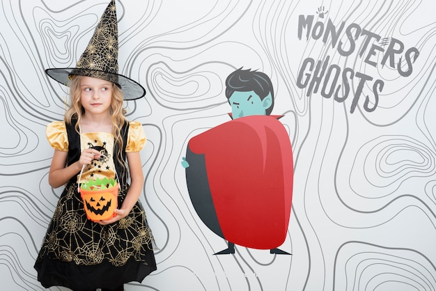 Cute girl dressed as a witch standing nearby an animated vampire Free Psd