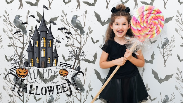 Cute girl holding a giant lollipop halloween event Free Psd