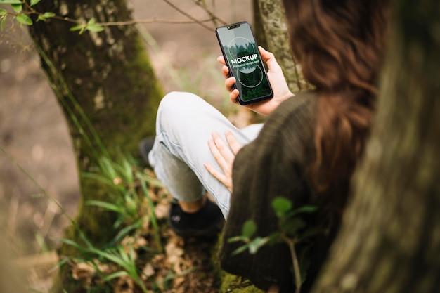 Милая женщина на природе с макетом смартфона Premium Psd